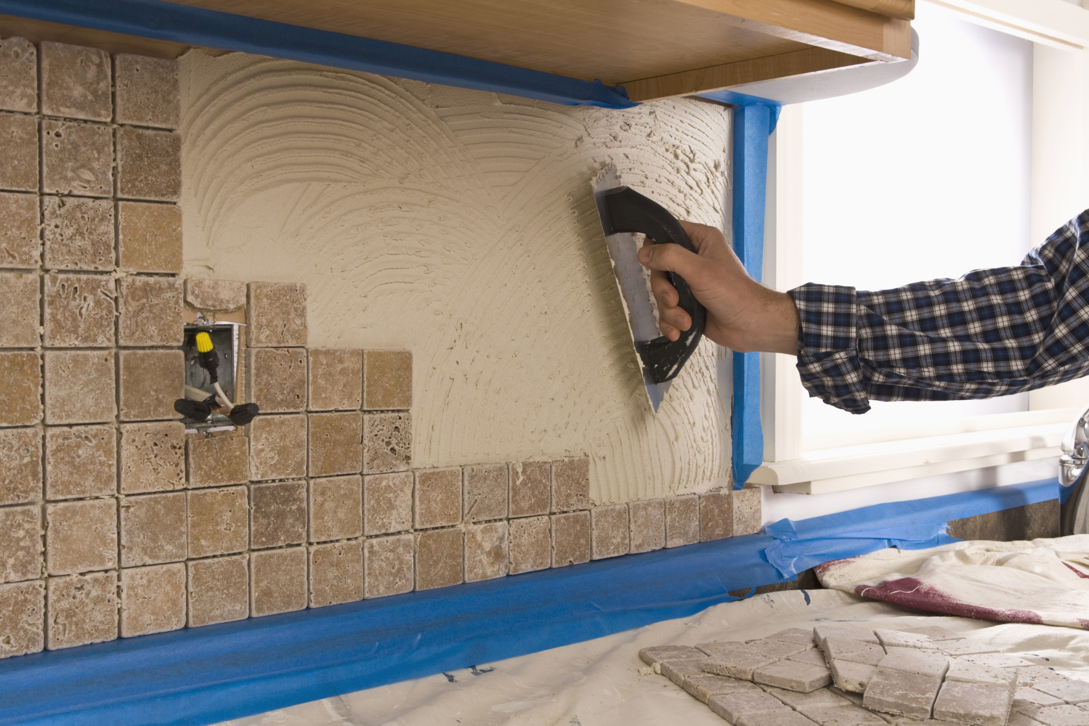 man putting tile on wall